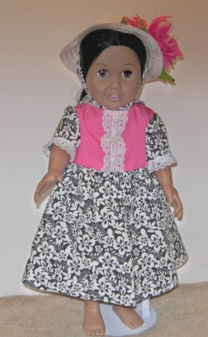 American Girl doll dress in flamingo and black and white flowers. A white straw hat with hot pink flowers.